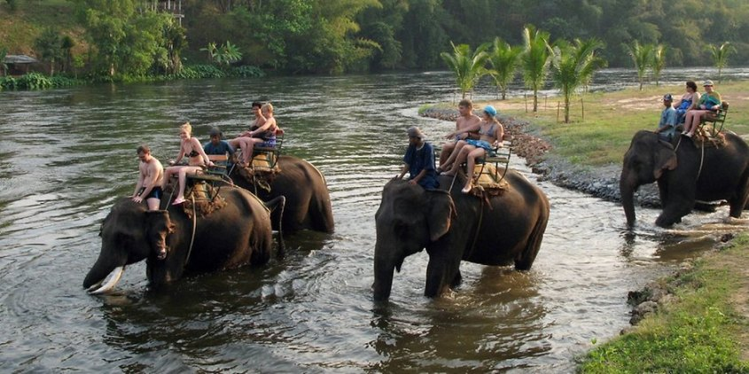 touristen-reiten-auf-elefant-durchs-wasser