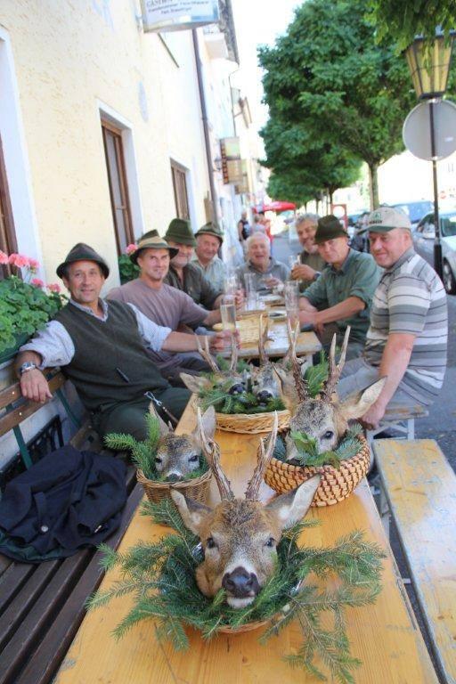 Jäger am Tisch mit Hirschköpfe